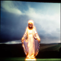 Glowing Virgin Mary figurine in landscape forground<br />