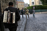 An accordionist walks through Montmartre, Paris, France, 15 September 2009