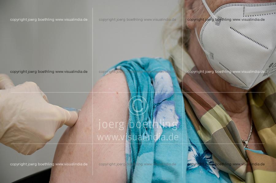 GERMANY, Hamburg, corona pandemic, largest vaccination center in germany, for daily max 7000 people / DEUTSCHLAND, Hamburg, Corona Pandemie, Impfzentrum der KVH und Sozialbehörde Hamburg in den Messehallen, groesstes Impfzentrum Deutschlands fuer bis zu 7000 Menschen taeglich, Impfung von alte Frau mit FFP2 Maske in der Impfkabine, Impfstoff Comirnaty EL 1491 von Biontech Pfizer,
