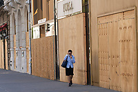 NEW YORK, NEW YORK - JUNE 08: A woman walks by  boarded up stores on June 08, 2020 in New York City. The City began first phase of reopening after nearly three months of shutdown , also Protests continue over black Americans abuse by the Police (Photo by Kena Betancur/VIEWpress via Getty Images)