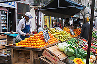A street market merchant with his stall selling fruits and vegetables, oranges, bananas, pumpkin... Montevideo, Uruguay, South America