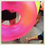 Tourists of Waikiki Beach carry their floatable beach toys.