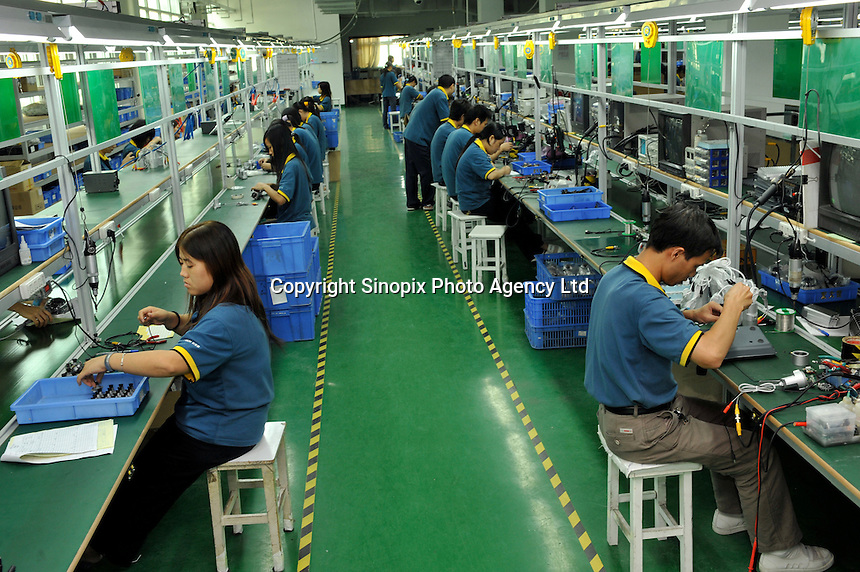 Workers inside CSST, China Security and Surveillance Technology, Shenzhen, China. The company specialises in making surveillance cameras..23 Oct 2008