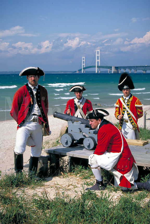 """Historic re-creation of British """"""""King's 8th Regiment of Foot"""""""" soldiers in 1774-81 era uniforms with Mackinac Bridge across Straits of Mackinac in background. Mackinaw City Michigan USA downtown."""