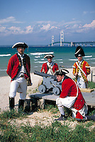 "Historic re-creation of British """"King's 8th Regiment of Foot"""" soldiers in 1774-81 era uniforms with Mackinac Bridge across Straits of Mackinac in background. Mackinaw City Michigan USA downtown."