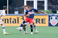 FOXBOROUGH, MA - JULY 25: Gustavo Bou #7 of New England Revolution passes the back to the midfield as Zorhan Bassong #19 of CF Montreal comes in to tackle during a game between CF Montreal and New England Revolution at Gillette Stadium on July 25, 2021 in Foxborough, Massachusetts.