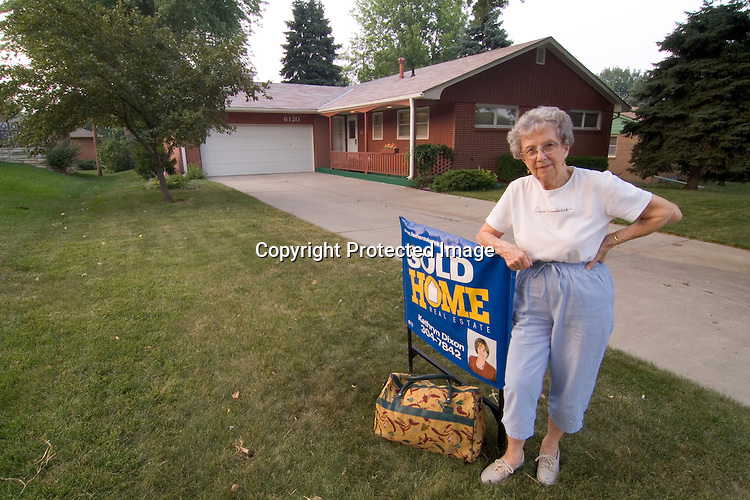 Elderly lady standing in front of her sold mid-1960s era home with her bag packed in Lincoln Nebraska.