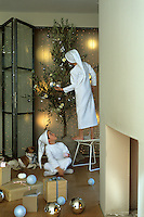 Two boys dressed as elves decorate an olive tree for Christmas in a room scattered with presents and baubles