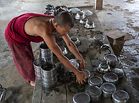Buddhist Monk Cleaning the pots after lunch break, Rakhine State, Myanmar