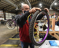 BIKES FOR ALL<br />Kyle Engler, a volunteer with Pedal It Forward, slips a tire on a bicycle wheel Saturday Nov. 14 2020 at the Pedal It Forward workshop in Rogers. Pedal It Forward provides bicycles to any adult or youngster who needs a bike. Volunteers assemble and repair donated bicycles at workshops in Rogers and Bentonville, said Eric Kinnison, assistant director at Pedal It Forward. The group will open a workshop soon in Joplin, Mo., Kinnison said. Go to nwaonline.com/201115Daily/ to see more photos.<br />(NWA Democrat-Gazette/Flip Putthoff)
