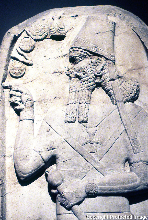 """Assyria:  Stele of Shamshi-Adad V--823-811 B.C.   (35 years after reign of Ashur Nasipal II). """" The King in an attitude of worship"""", he holds a mace, symbol of authority. Maltese cross on chest is a symbol of sun god."""