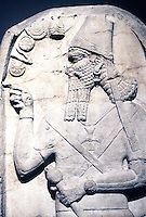 "Assyria:  Stele of Shamshi-Adad V--823-811 B.C.   (35 years after reign of Ashur Nasipal II). "" The King in an attitude of worship"", he holds a mace, symbol of authority. Maltese cross on chest is a symbol of sun god."