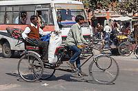 Jaipur, Rajasthan, India.  Mid-day Street Traffic in Central Jaipur.  Two Men Enjoying a Rickshaw Ride.