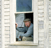 Man looks out of window of an old house in the country. Tom Harding. Arkansas.