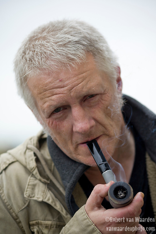 A grey haired man smoking a pipe in Ramsgate, the  United Kingdom.