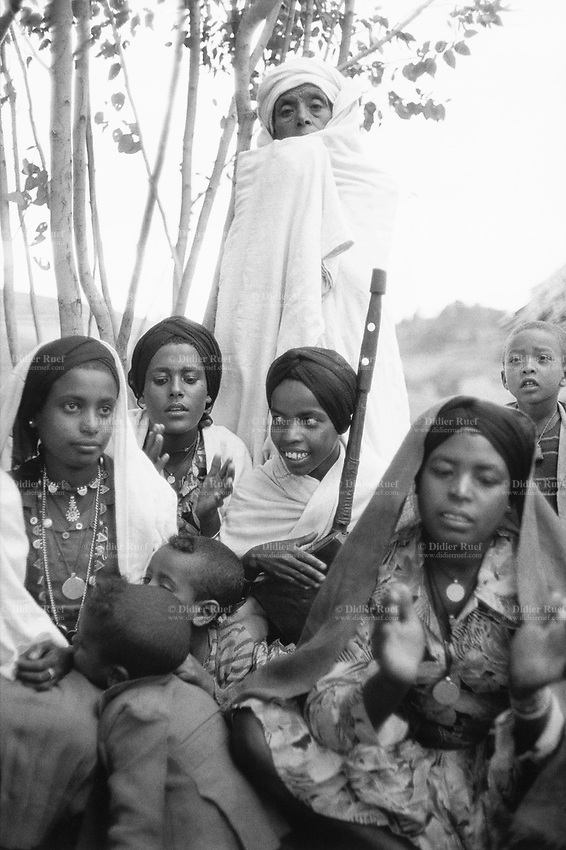 Ethiopia. West Gujam.Danbecha district. Anjeni is a small village. Wedding ceremony. The young bride ( 13 years old, first on the left) seats with some friends. Her brothers and sisters sing and play music. Her old grandmother stands up and covers her face with a white loincloth and veil. The bride waits for her groom to take her to his parents' place. © 1996 Didier Ruef