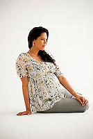 Pregnant Hispanic woman, sitting down
