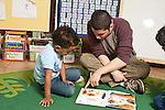 Education Preschool Headstart 3-4 year olds young male teacher reading book to boy pointing at page
