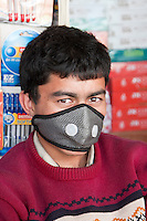 Kathmandu, Nepal.  Nepali Book Store Salesman, Wearing Breathing Mask to Protect Against Air Pollution.