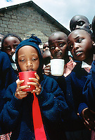 Kenya. Rift Valley Province. Nyahururu. Nyandarva boarding primary school. At break time, the pupils drink porridge.  The boys and girls wear a colorful uniform. A young boy holds in his hands a red cup and wears a blue hat and a red tie.© 2004 Didier Ruef