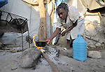 A woman heats water for a meager breakfast for her family in a camp in Grand-Goave, Haiti, for families left homeless by the January 2010 earthquake. The ACT Alliance has supported families in this camp with a variety of services, and has rebuilt a school beside the tent city.
