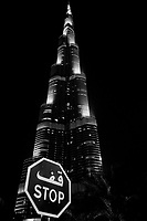 United Arab Emirates (UAE). Dubai. The Burj Khalifa, known as the Burj Dubai prior to its inauguration in 2010, is a skyscraper. With a total height of 829.8 m and a roof height (excluding antenna, but including a 244 m spire of 828 m, the Burj Khalifa has been the tallest structure and building in the world since its topping out in 2009. The Y-shaped tripartite floor geometry is designed to optimize residential and hotel space. A buttressed central core and wings are used to support the height of the building. A road sign with the words Stop written in arabic and english languages. The United Arab Emirates (UAE) is a country in Western Asia at the northeast end of the Arabian Peninsula. 16.02.2020  © 2020 Didier Ruef