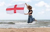 BNPS.co.uk (01202) 558833. <br /> Pic: CorinMesser/BNPS<br /> <br /> Pictured: Mya Punter-Bradshaw, 21, flying the flag for England on a very windy day in Boscombe, Dorset. <br /> <br /> England fans visiting the beaches of Bournemouth, Dorset show their support for the team ahead of the Euro 2020 semi-final against Denmark Tomorrow (Wed).