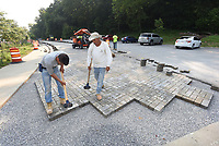 PAVING THE WAY <br />Rene Pichardo (left) and Artemio Estrada with 4G Paving set paving stones on Tuesday July 20 2021 while building a porous parking area at Lake Atalanta Park in Rogers. Two poruous parking lots will be part of the park using designs provided by the Beaver Watershed Alliance. The design allows water to soak into the ground to reduce runoff into the spring-fed stream that flows into Lake Atalanta. After leaving the lake, the stream flows into Beaver Lake in the Prairie Creek area. Lake Atalanta was built in 1936 by the Works Progress Administration as part of President Franklin D. Roosevelt's New Deal, according to signs at the park. The lake is named for Atalanta Gregory, wife of O.L. Gregory who donated most of the land that is now the 236-acre park one-half mile east of downtown Rogers. Go to nwaonline.com/210721Daily/ to see more photos.<br />(NWA Democrat-Gazette/Flip Putthoff)