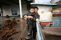 CHINA. Hubei Province. A man and his son in a village near the 3 Gorges.  The flooding of the three Gorges, by damming the Yangtze near the town of YiChang, has remained a controversial subject due to the negative environmental consequences and the displacement of millions of people in the flood plain. The Yangtze River however is reported to be at its lowest level in 150 years as a result of a country-wide drought. It is China's longest river and the third longest in the world. Originating in Tibet, the river flows for 3,964 miles (6,380km) through central China into the East China Sea at Shanghai.  2008.