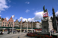 Belgium statue called The Visitors and old buildings in the colorful city of Bruges