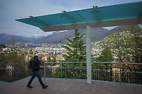 """Switzerland. Canton Ticino. Lugano. A man wearing a mask on the face to protect himself from Coronavirus (also called Covid-19) walks by a bus stop at the railway station. Nobody is waiting for the platform. Due to the spread of the coronavirus, the Federal Council has categorised the situation in the country as """"extraordinary"""". It has issued a recommendation to all citizens to stay at home, especially the sick and the elderly. The Federal Council (German: Bundesrat, French: Conseil fédéral, Italian: Consiglio federale, Romansh: Cussegl federal) is the seven-member executive council that constitutes the federal government of the Swiss Confederation. From March 16 the government ramped up its response to the widening pandemic, ordering the closure of bars, restaurants, sports facilities and cultural spaces. Only businesses providing essential goods to the population – such as grocery stores, bakeries and pharmacies – are to remain open. 27.03.2020 © 2020 Didier Ruef"""