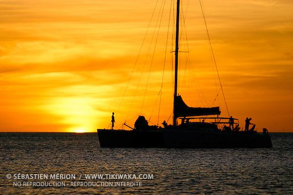 Catamaran au coucher de soleil,  îlot Ua (Cinq îles), lagon sud, Nouvelle-Calédonie