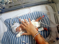 """COPY BY TOM BEDFORD<br /> Pictured: The premature baby of Luc Protheroe and partner Paighton Waters at the Royal Gwent Hospital in Newport, Wales, UK <br /> Re: A young couple were granted their Christmas wish to cwtch their """"miracle"""" baby for the first time.<br /> Little Flynn Protheroe was the same size as a mobile phone when he was born 14 weeks early.<br /> The tiny baby and his mother Paighton Waters, 19, were both given a 50-50 chance of surviving after a rare placental abruption.<br /> Flynn was born by Caesarian and doctors worked on him for 20 minutes to get his tiny heart and lungs working.<br /> Meanwhile Paighton was on the critical list after losing four litres of blood.<br /> But five weeks later the pair are doing well and have been allowed to hold their little boy for a Christmas cuddle.<br /> Proud dad Luc Protheroe, 21, said: """"It's a miracle, I could have lost them both."""