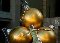 A statue of a young child is framed in front of large gold Christmas ornaments outside of the Wachovia corporate headquarters in Uptown Charlotte.
