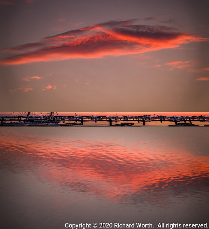 A cloud at sunset is reflected in the water below on a summer evening at a marina along San Francisco Bay.