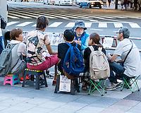 A street caricaturist surrounded by his clients. 500 yen per portrait.