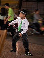 A young street performer at night in the streets of saigon performing a Michael Jackson act.<br /> Street Life in Saigon or in Vietnamese Ho Chi Minh City where old and new architecture mix in harmony. The bustling Metropolis of South Vietnam.