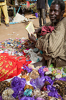 Senegal, Touba.  Street Vendor of Ear Rings and Costume Jewelry Reading a Booklet in Arabic.