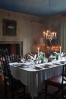 Illuminated with soft candlelight, the atmospheric dining room is lined with Jacobean wood panelling