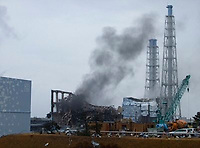 In this photo released by Tokyo Electric Power Co. (TEPCO), gray smoke rises from Unit 3 of the tsunami-stricken Fukushima Dai-ichi nuclear power plant in Okumamachi, Fukushima Prefecture, Japan, Monday, March 21, 2011. Official says the TEPCO temporarily evacuated its workers from the site. At left is Unit 2 and at right is Unit 4. (AP Photo/Tokyo Electric Power Co.) EDITORIAL USE ONLY
