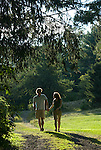 Couple running down path holding hands