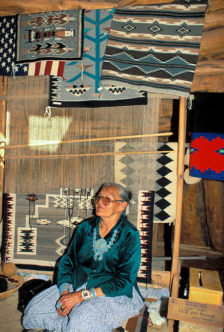 Navajo weaver sits next to her weaving loom and traditional rugs for sale inside her hogan at Monument Valley