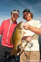 Fishing buddies hoisting smallmouth bass