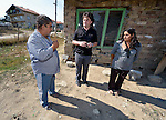 """Vassil Ivanov (left) lives in the Bulgarian town of Staro Oriahovo, where residents consider the term """"Roma""""  to be negative and thus refer to themselves as Romanian-speaking Bulgarians. Ivanov is a member of the local United Methodist Church. Here he talks in front of his home with his adult daughter, Pauna Vassilev (right), who most of the year works as a elder caregiver in Greece, and with the Rev. Daniel Topalski, the superintendent of the United Methodist Church in Bulgaria. ."""