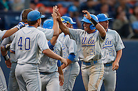 Brian Carroll #24 of the UCLA Bruins is greeted by his teammates including Nick Vander Tuig #21 after scoring against the Cal State Fullerton Titans during the NCAA Super Regional at Goodwin Field on June 7, 2013 in Fullerton, California. UCLA defeated Cal State Fullerton, 5-3. (Larry Goren/Four Seam Images)