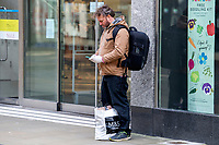 Pictured: A man with gloves on checks his phone in Swansea City Centre during the Covid-19 Coronavirus pandemic in Wales, UK, Swansea, Wales, UK. Monday 23 March 2020