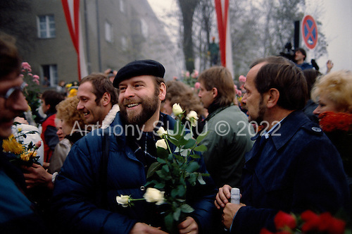 Lichterfelde, Berlin (West) and Teltow, Potsdam (East) crossing post, Germany<br /> November 14, 1989 <br /> <br /> East and West Germans greet each other with flowers as they cross the border near the Berlin Wall. Germans gathered as the wall is dismantled and the East German government lifts travel and emigration restrictions to the West on November 9, 1989.