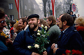 Ostpreu Bendamm, Germany<br /> November 14, 1989 <br /> <br /> East and West Germans greet each other with flowers as they cross the border near the Berlin Wall. Germans gathered as the wall is dismantled and the East German government lifts travel and emigration restrictions to the West on November 9, 1989.