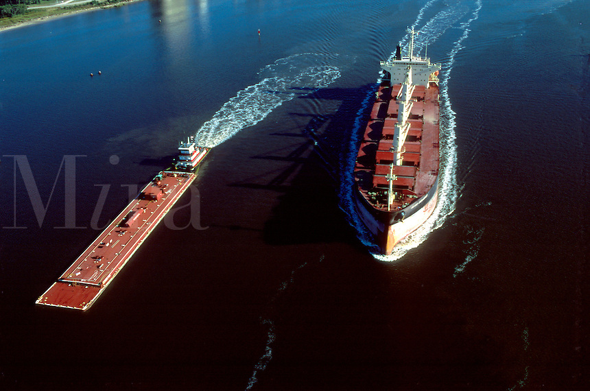 Aerial view of a cargo ship and barge.