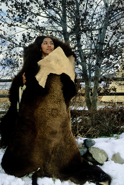 Shoshone-Cree woman wrapped in a large buffalo robe during a cold winter day. Model released
